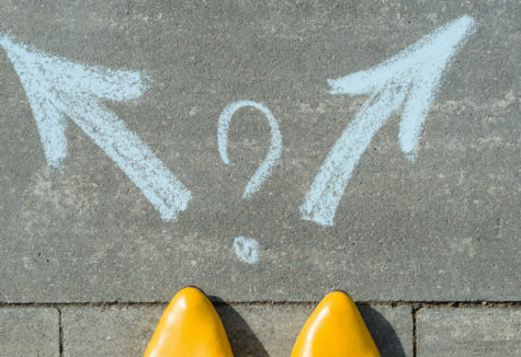 The tips of yellow pointed shoes in front of two chalk arrows pointing both left and right with a question mark between them.