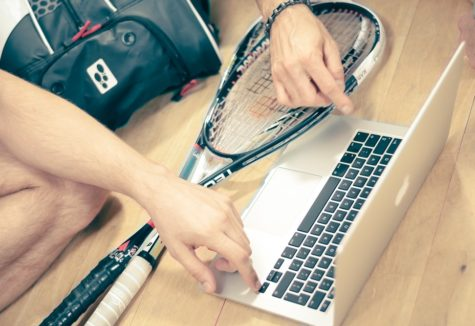 Two squash players with their equipment gathered around a laptop computer.