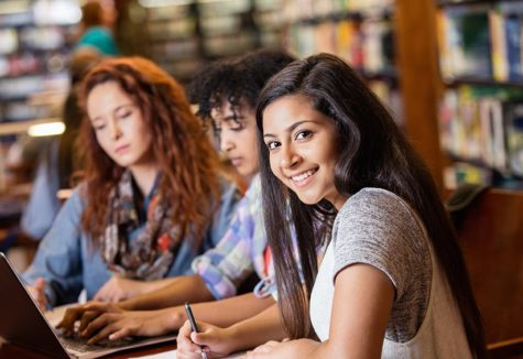 three high-school girls studying in their school library.