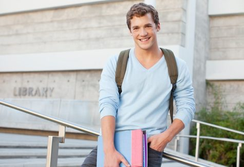 a high-school boy in a blue sweater standing outside his local library.