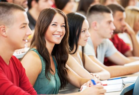 A female student smiling while in a lecture hall with many other students.