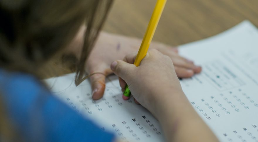A young student erasing an answer from a standardized testing answer sheet.
