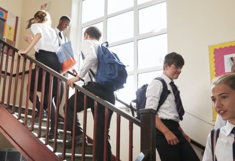 Private school students going up and down a school staircase.