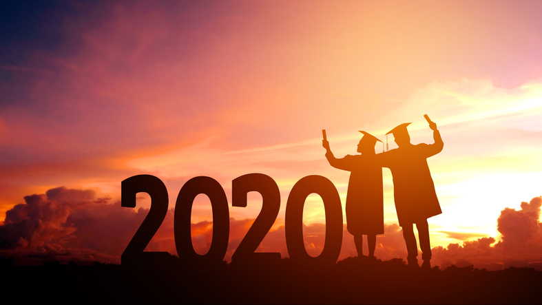 Two graduates next to large numbers saying '2020' backlit by a fiery sunset.