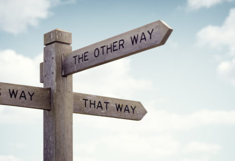 A wooden signpost that mark 'This Way', 'That Way', and 'The Other Way'.