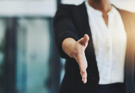 A professional businesswoman extending her hand.