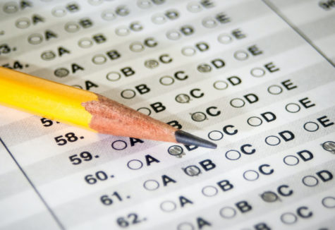 A closeup image of a pencil laying on a multiple-choice answer form.