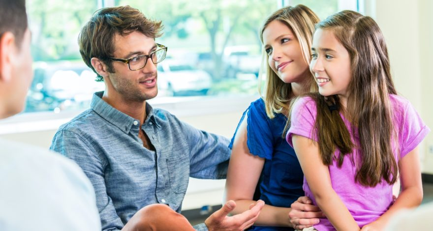 A couple and their young daughter sitting and talking with a consultant.