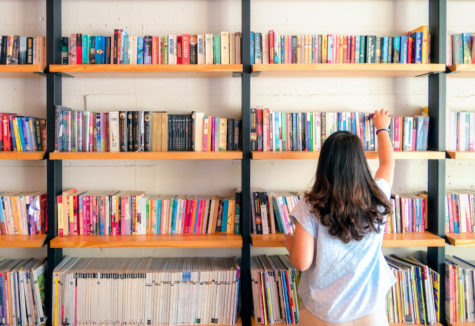 A female perusing through many books stacked on a wall full of bookshelves.