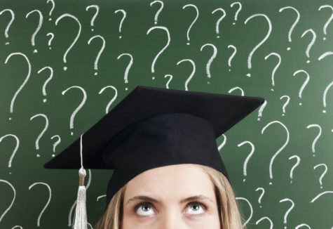 A graduating senior in her cap standing in front of a chalk board covered in question marks.