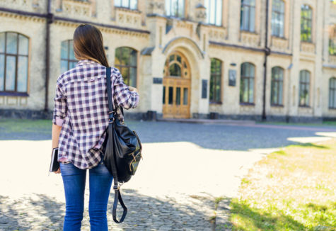 A female student preparing to enter a large stone-fronted university building.