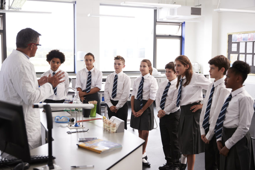 A group of private school students around their chemistry teachers desk.