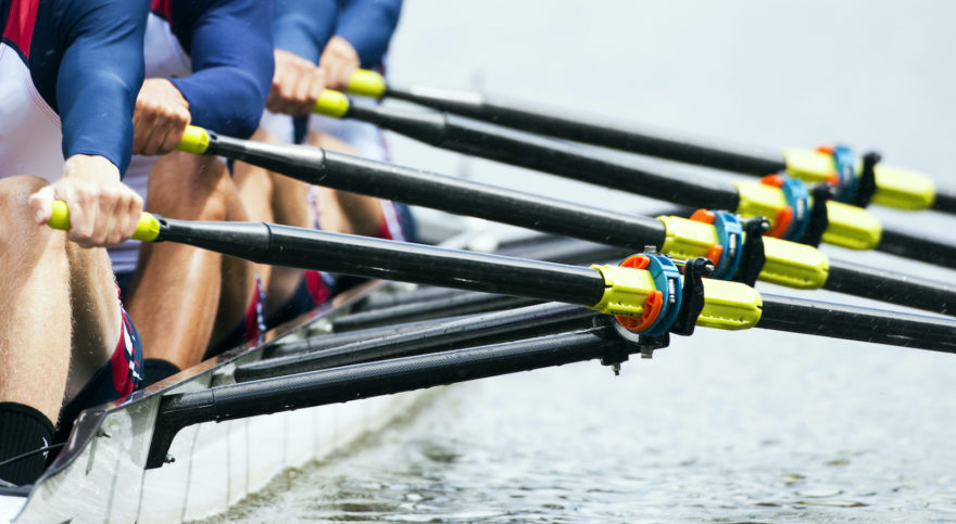 A Crew team practicing on a body of water with the focus on their oarlocks.