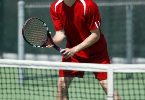 A man playing tennis up close to the net.