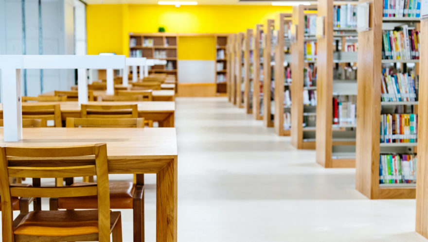 Looking down the walkway of a college library with shelves on the right and reading desks on the left.