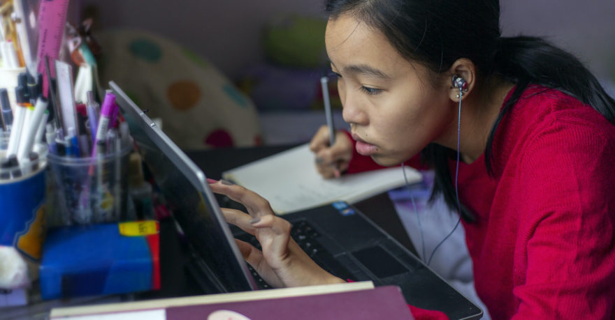 A female student of Asian descent studying hard at her laptop while taking notes in a notebook.