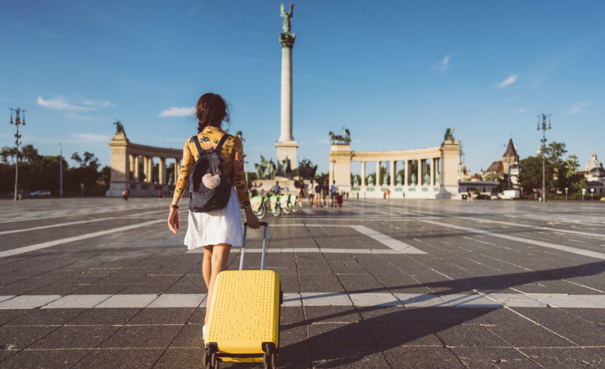 A female pulling her yellow rolling suitcase across a town square in a foreign city.