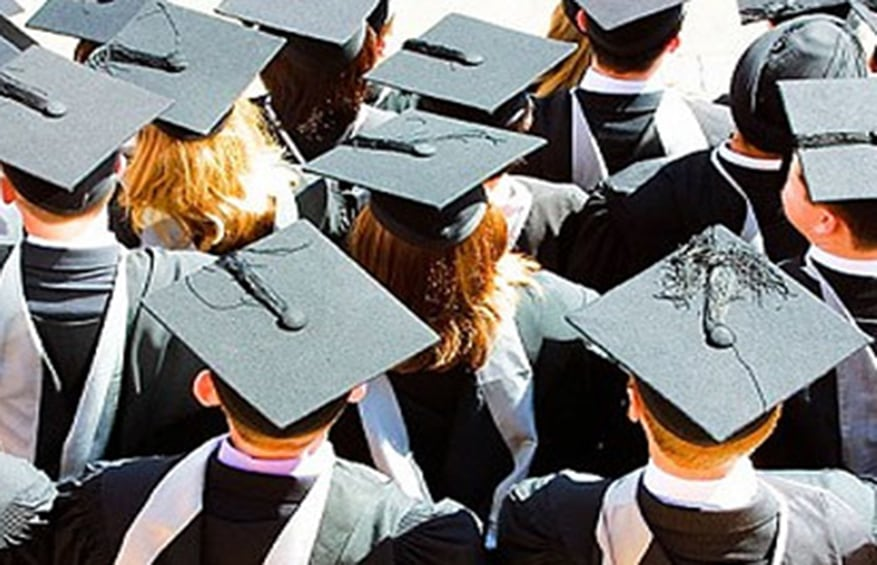 students lined up for high-school graduation in their cap and gown.