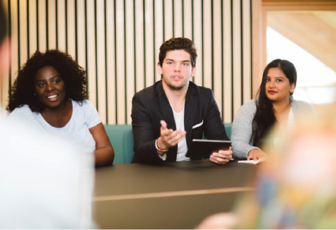 Three students, two female one male, presenting something to a group from across a conference table.