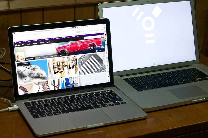 Two Macbook Pro laptops on a desk transferring data from one to the other.