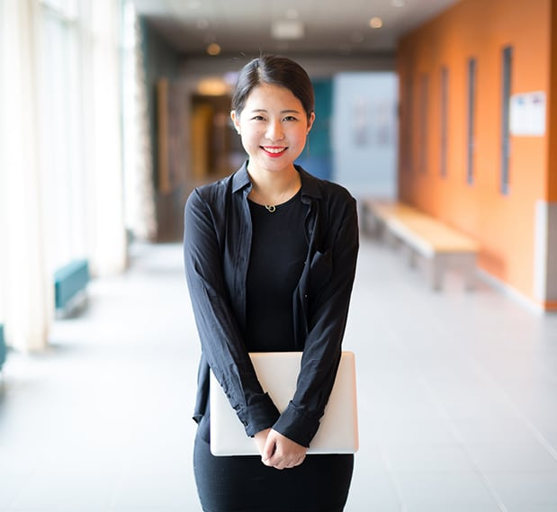 Smiling female teen of Asian descent standing in school hallway holding laptop near waist