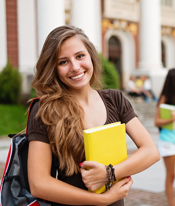 Smiling brunette female college student standing outside building on campus with friends in background