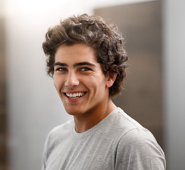 Smiling male college student of multiethnic descent with short, curly brown hair