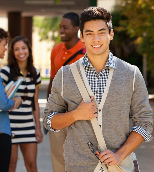 Smiling teenage boy of Asian descent standing outside school with classmates in background