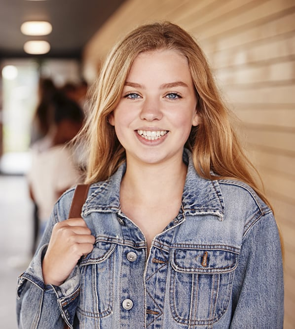 Smiling young blonde high school girl standing in hallway at school with other students behind her