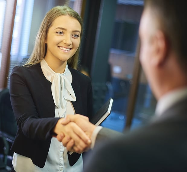Teen girl in business clothes shaking hands with older man at college interview