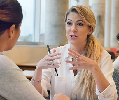 Blonde female college counselor seated at table talking to student