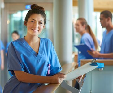 Smiling female med student in scrubs standing at nurse's station with other people in scrubs behind her