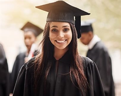 Smiling high school girl of Indian descent wearing graduation cap and gown with classmates in background