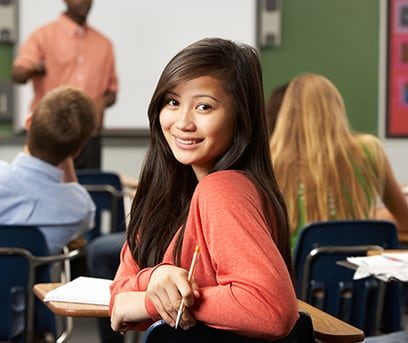 A teenage female student in a classroom turning in her desk seat to look at you.