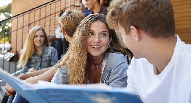 High school girl and boy sitting and talking on steps at school with friends in background