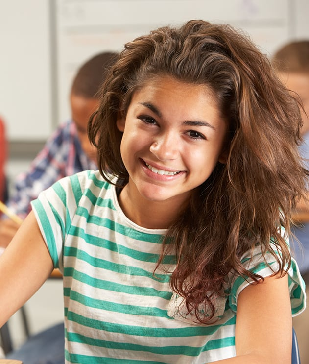 Smiling young multiracial teen girl seated at desk in classroom
