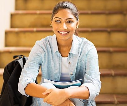 Smiling teen girl of Indian descent sitting on stairs inside school