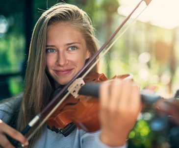 Close-up of high school girl with long blonde hair playing violin