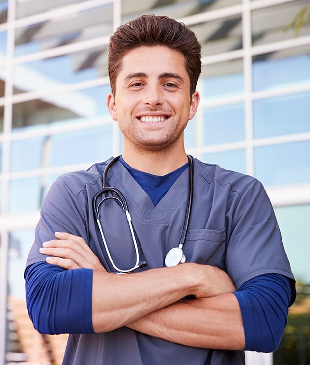 Smiling male med student in scrubs standing outside hospital