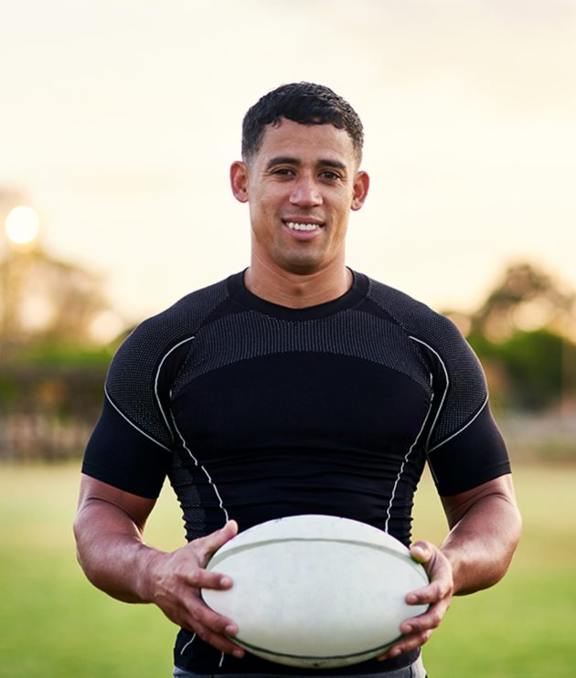 Smiling college rugby player standing on field holding rugby ball