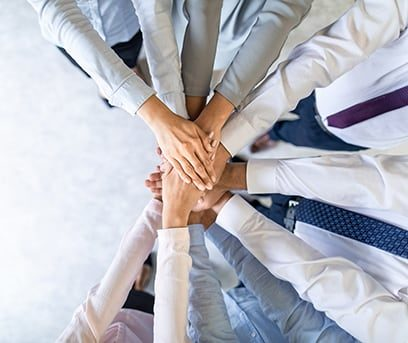 A team putting their hands together in a stack in a show of team spirit.