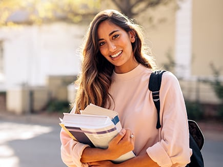 A female student carrying school books.